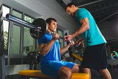 Athlete muscular bodybuilder and personal trainer  in the gym training with Stock Photos