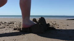 Child Stepping On A Sandcastle On A Sunny Beach Stock Footage