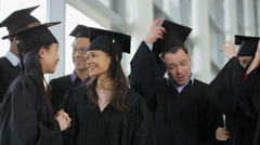 4K Happy group of mature students on graduation day, throwing caps into the air Stock Footage