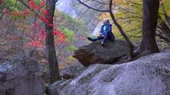 Tourist  girl  enjoys the autumn nature on a big stone in Seoraksan NP Stock Footage