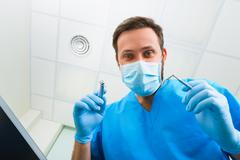 Dentist leaned over patient in dentist's chair at clinic. Doctor with mask and - stock photo