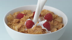 Corn flakes with raspberry in a bowl pouring with milk. Slow Motion. Stock Footage