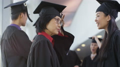 4K Happy group of mature students on graduation day, 2 women smile to camera - stock footage