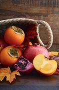 Basket of fresh persimmons and pomegranates - stock photo