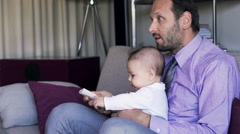 Young father with baby boy watching TV on sofa at home Stock Footage