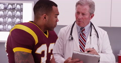 Senior white male doctor consulting black sports athlete's injury Stock Footage