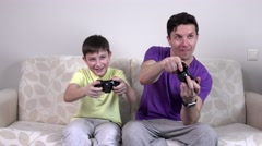 Man and young boy with video game controllers smiling Stock Footage