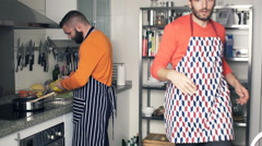 Two male friends in aprons cooking in kitchen Stock Footage