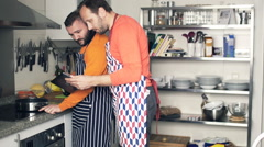 Two male friends in aprons cooking and checking recipe on tablet in kitchen - stock footage
