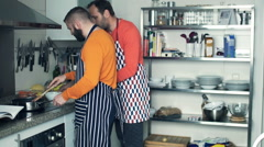Two male friends in aprons cooking and checking recipe in cookbook in kitchen Stock Footage