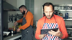 Two male friends in aprons cooking and using tablet computer in kitchen Stock Footage