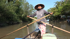 Vietnamese woman rows traditional wooden boat through Mekong Delta Stock Footage