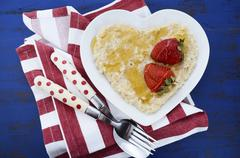 Plate of nutritious and healthy cooked breakfast oats with strawberries and h Stock Photos