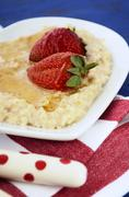 Plate of nutritious and healthy cooked breakfast oats with strawberries and h - stock photo