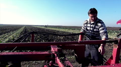 Young farmer cleaning the land cultivating machine on field. Stock Footage