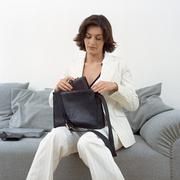 Woman puts diary in handbag Stock Photos