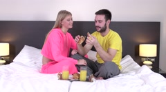 Couple snuggled under duvet eating breakfast Stock Footage