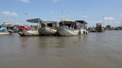Sailing past wooden cargo vessels at floating market in Mekong Delta, Vietnam Stock Footage