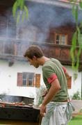 Young male cooks on barbeque - stock photo
