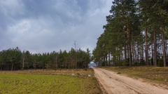 4k timelapse of rural landscape with sandy road, field and forest Stock Footage