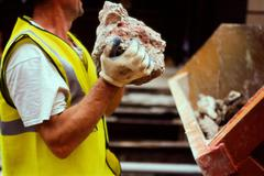 Construction worker holding rubble - stock photo