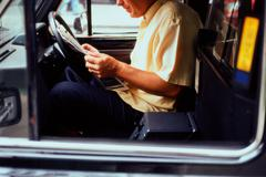 Taxi driver reading a newspaper Stock Photos