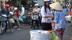 Woman buys fresh French bread from a local street vendor in Vietnam Stock Footage