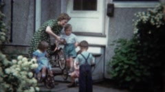 1944: Mother readies tricycle bike for kids playing outside family home.  Stock Footage