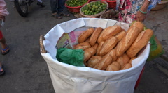 Fresh French style bread for sale at a local food market in Vietnam Stock Footage