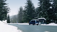 Minivan Passes Bus Shelter In Snowy Landscape Stock Footage