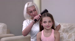 Stock Video Footage of Mom makes daughter hairstyle