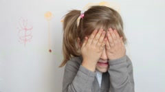 Pretty little girl closing her face palms Stock Footage