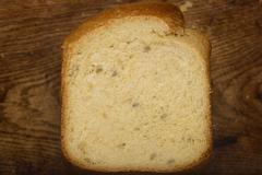 home-made bread from a bread machine on the kitchen board - stock photo