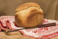 home-made bread from a bread machine on the kitchen table with a board - stock photo