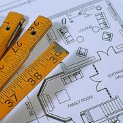 Extendable ruler and architectural blueprints - stock photo