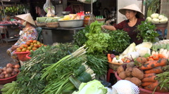 Women sell fresh green vegetables at the market in Vietnam, Southeast Asia Stock Footage