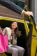 Female shopper leaving taxicab - stock photo