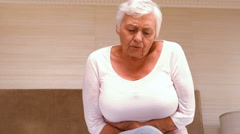 Old woman having a huge stomach pain Stock Footage