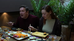 Man and woman eating sushi and rolls with green tea. Stock Footage
