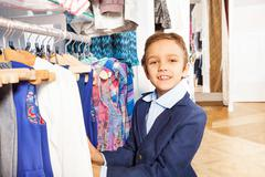 Small boy in navy suit standing near clothes Stock Photos