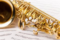 Beautiful golden alto saxophone on musical notes Stock Photos