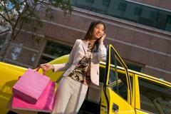 Woman leaving taxicab with shopping bags - stock photo