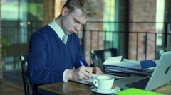 Businessman writing something in the notebook and drinking coffee, steadycam sho Stock Footage