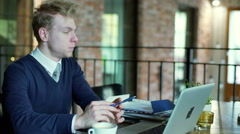 Businessman waiting for someone in the cafe and looking annoyed, steadycam shot Stock Footage