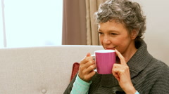 Woman drinking hot beverage Stock Footage