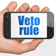 Political concept: Hand Holding Smartphone with Veto Rule on display - stock illustration