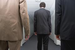 Three businessmen standing in corridor Stock Photos