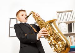 Boy in school uniform playing on alto saxophone - stock photo