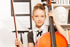 Portrait of girl holding fiddle-bow to play cello - stock photo
