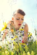 Pin up Girl with a suicide roll on a wildflower meadow with backlight - stock photo